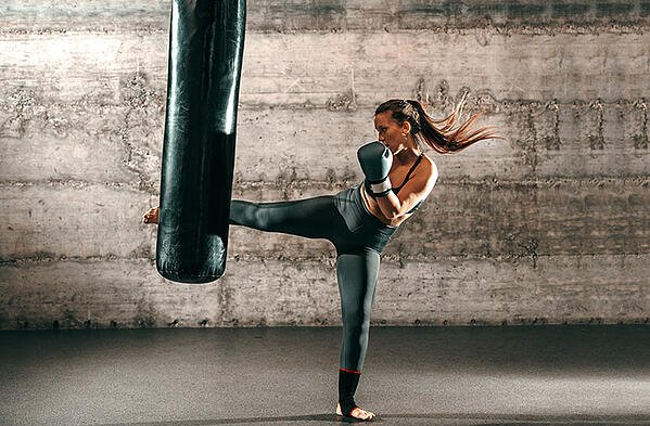 woman doing cardio kicboxing on a punching bag