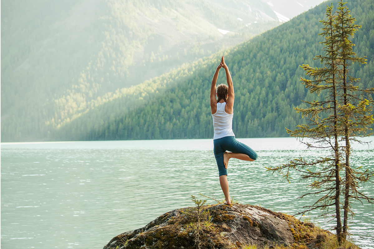 yoga instructor posing in front of a peaceful lake setting