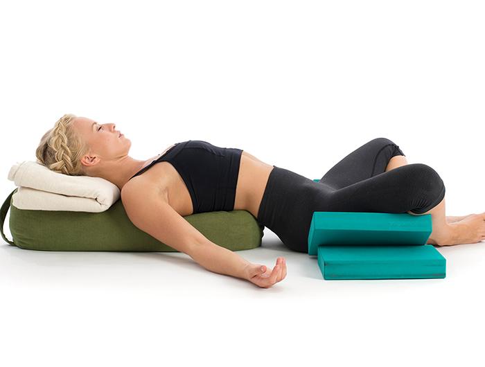 woman lying on her back doing restorative yoga