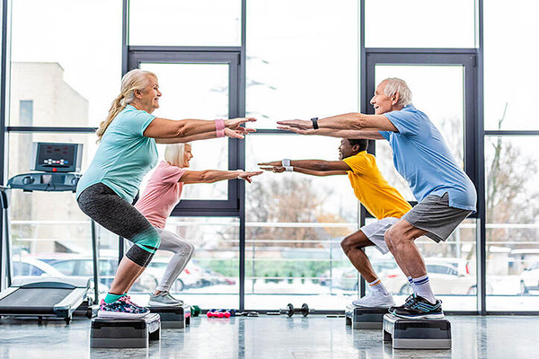 a group of four seniors doing pilates